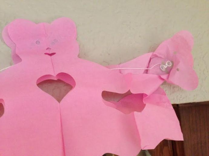 An inconspicuous pushpin into the brain of the pink teddy bear on the end of the 9-foot banner